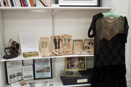 Objects on display in the New Century exhibit include vintage irons, sewing patterns and clothing.
